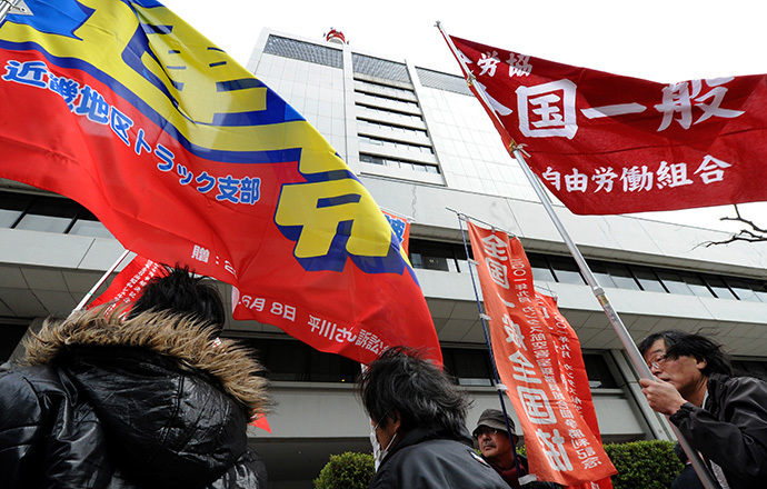 Fukushima nuclear power workers and their supporters hold flags in front of the headquarters of Tokyo Electric Power Company (TEPCO), operator of the tsunami-battered Fukushima Daiichi nuclear power plant, during a rally in Tokyo on March 14, 2014 (AFP Photo / Toru Yamanaka)