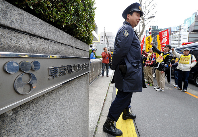 Security stands outside as Fukushima nuclear workers (behind) and their supporters shout slogans and raise their fists in front of the headquarters of Tokyo Electric Power Company (TEPCO), operator of the tsunami-battered Fukushima Daiichi nuclear power plant, during a rally in Tokyo on March 14, 2014 (AFP Photo / Toru Yamanaka)