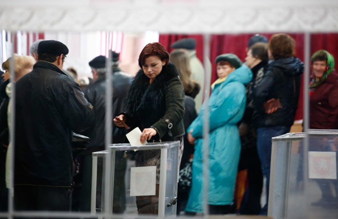 A woman is reflected in a mirror as she casts her ballot during voting in a referendum at a polling station in Simferopol March 16, 2014.(Reuters / Thomas Peter)