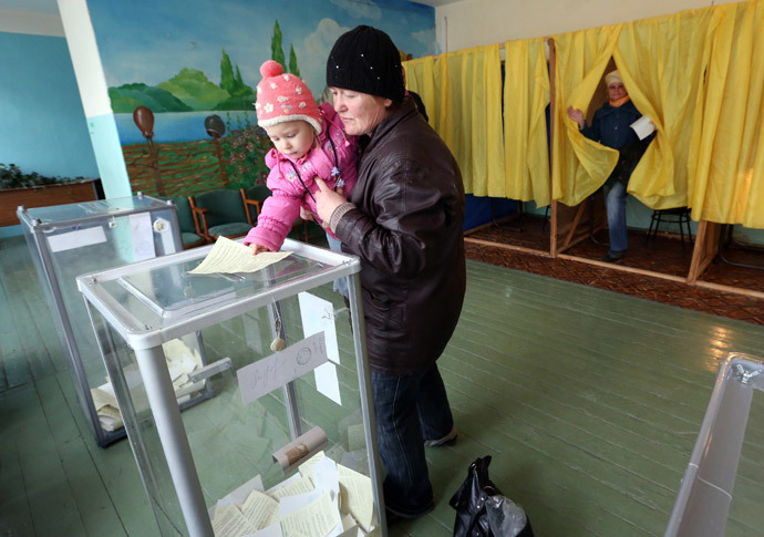 A child holds the ballot of his mother during the referendum on the status of Ukraine's Crimea region at a polling station in Bakhchisaray March 16, 2014.(Reuters / Sergei Karpukhin)