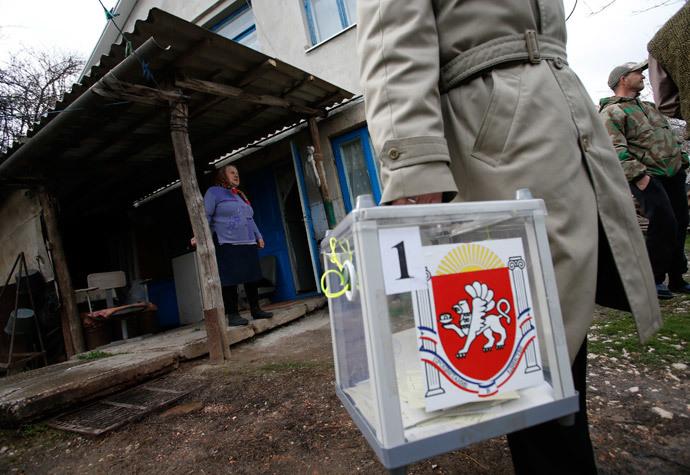 An election official carries a mobile ballot box after a house visit during voting in a referendum in Dobroye outside Simferopol March 16, 2014.(Reuters / David Mdzinarishvili)