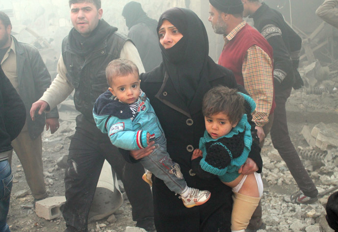 A file photo taken on December 15, 2013 shows a Syrian woman carrying children following airstrikes in northern city of Aleppo. (AFP Photo / Mohammed Al-Khatieb)