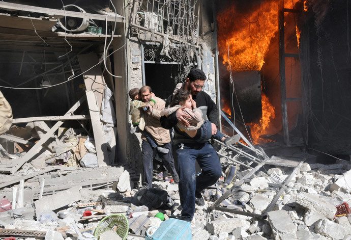 Men carrying children run out of a burning building following a barrel bomb attack in the northern Syrian city of Aleppo on February 8, 2014. (AFP Photo / Baraa Al-Halabi)