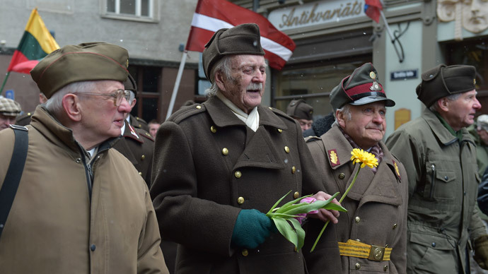Man dressed in pre-WWII Latvian military uniforms walk along with veterans of the Latvian Legion, a force that was commanded by the German Nazi Waffen SS, and their sympathizers to the Monument of Freedom in Riga, Latvia on March 16, 2014.(AFP Photo / Ilmars Znotinsa)