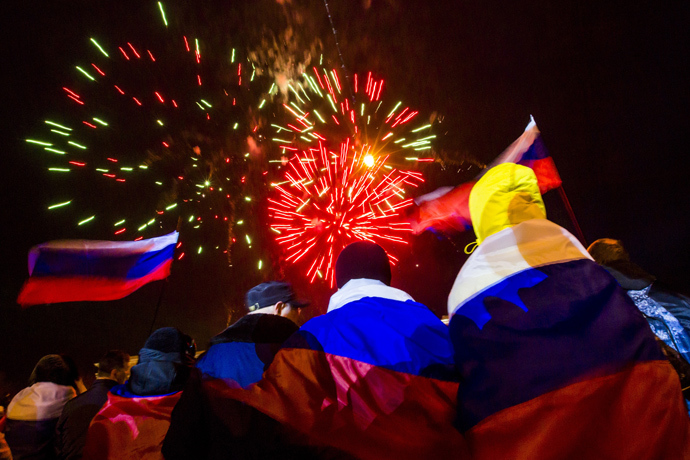 People wrapped with Russian flags watch fireworks during celebrations after the preliminary results of today's referendum are announced on Lenin Square in the Crimean capital of Simferopol March 16, 2014 (Reuters / Thomas Peter)