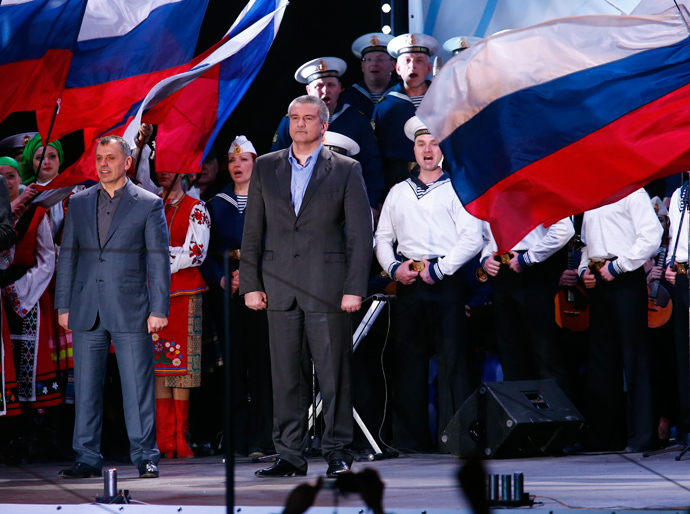 Crimean Prime Minister Sergey Aksyonov (C) stands on a stage as preliminary results of today's referendum are announced on Lenin Square in the Crimean capital of Simferopol March 16, 2014 (Reuters / Thomas Peter)