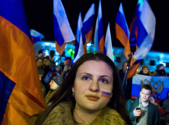 A woman with her face painted in the colours of the Russian national flag waits for the announcement of preliminary results of today's referendum on Lenin Square in the Crimean capital of Simferopol March 16, 2014 (Reuters / Thomas Peter)