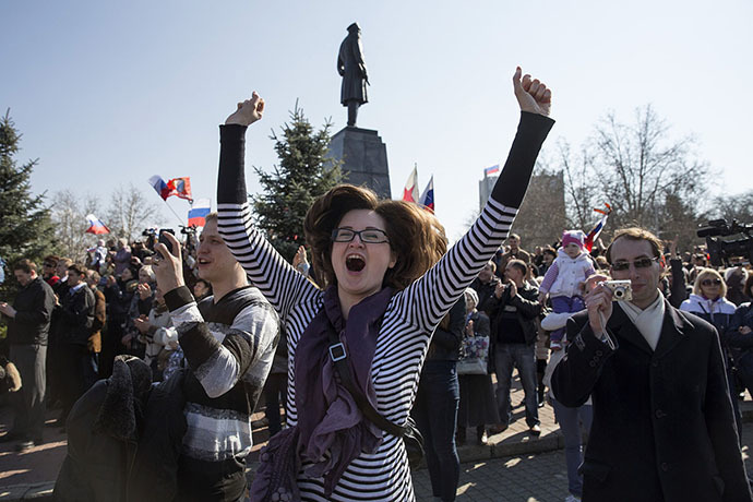 A woman jumps for joy during a broadcast of Russian President Vladimir Putin's address to the Federal Assembly in Sevastopol March 18, 2014. (Reuters / Baz Ratner)