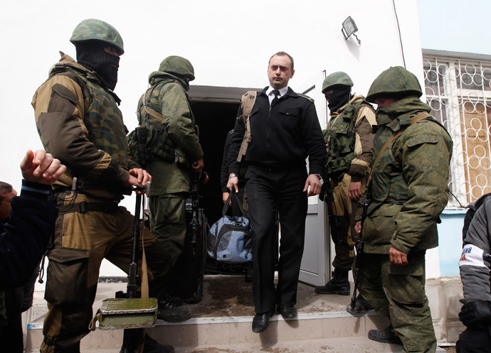 A Ukrainian naval officer (C) passes by armed men, believed to be Russian servicemen, as he leaves the naval headquarters in Sevastopol, March 19, 2014. (Reuters / Vasily Fedosenko)
