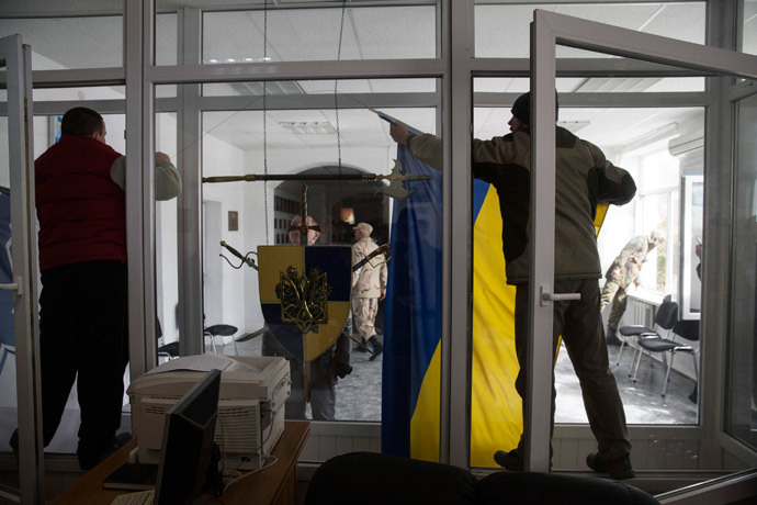 A pro-Russian supporter takes down a Ukrainian flag after breaking into the territory of the naval headquarters in Sevastopol, March 19, 2014. (Reuters / Baz Ratner)