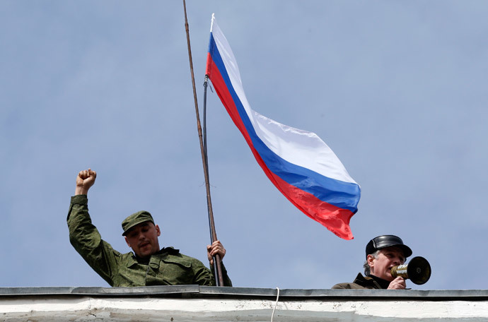 A man holds a Russian flag on the roof of the naval headquarters in Sevastopol, March 19, 2014. (Reuters / Vasily Fedosenko)