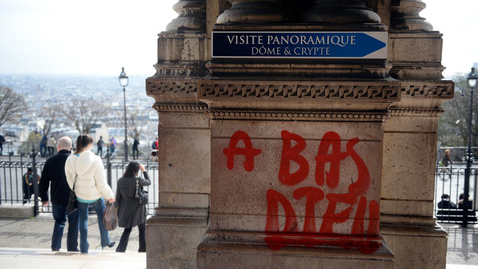 "People walk past grafittis reading ""Down with god"" written on the Sacre-Coeur Basilica in the Montmartre area in Paris on March 19, 2014.(AFP Photo / Martin Bureau)"