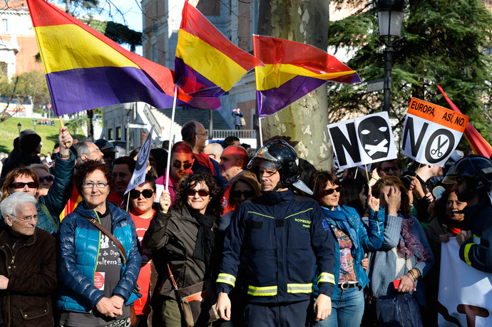 "A fireman stands in front of demonstrators, some of them waving flags of the Spanish second republic, during a march dubbed ""the Marches for Dignity 22-M"" to protest against austerity in Madrid on March 22, 2014. (AFP Photo / Gerard Julien)"