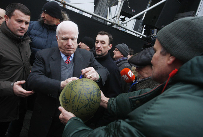 US Senator John McCain (2nd L) signs a military helmet for a protester at Independence Square in Kiev on December 15, 2013. (AFP Photo / Yuriy Kirmichny)