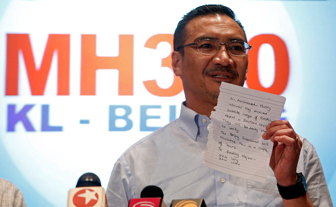 Malaysia's acting Transport Minister Hishammuddin Hussein holds up a note that he has just received on a new lead in the search for the missing Malaysia Airlines Flight MH370, during a news conference at Kuala Lumpur International Airport March 22, 2014. (Reuters / Edgar Su)