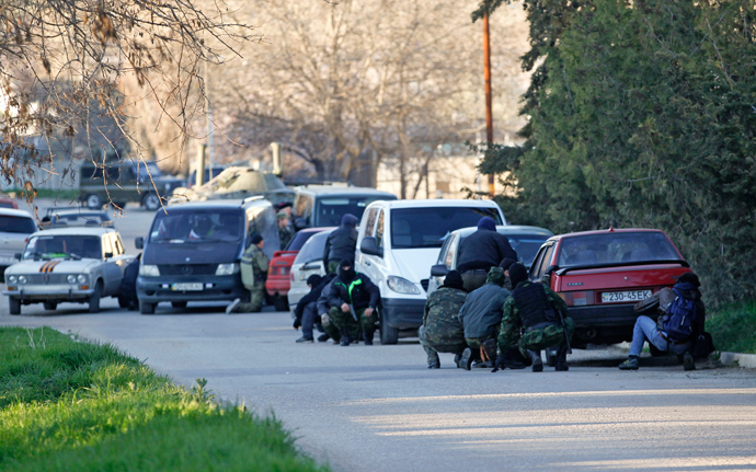 Members of Crimea's self-defense units take cover behind cars outside a military base in the Crimean town of Belbek near Sevastopol March 22, 2014 (Reuters / Vasily Fedosenko)