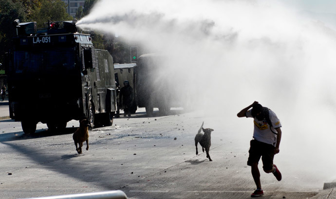 A water cannon disperses demonstrators during a protest to demand free and good quality education and a call for a Constituent Assembly, in Santiago, on March 22, 2014. (AFP Photo / Martin Bernetti)