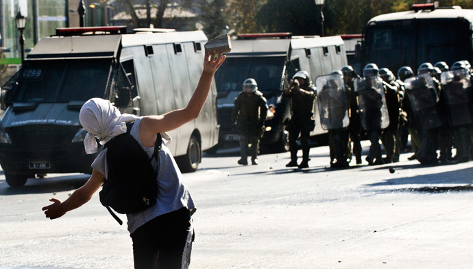 A demonstrator throws stones to riot policemen during a protest to demand free and good quality education and a call for a Constituent Assembly, in Santiago, on March 22, 2014. (AFP Photo / Martin Bernetti)