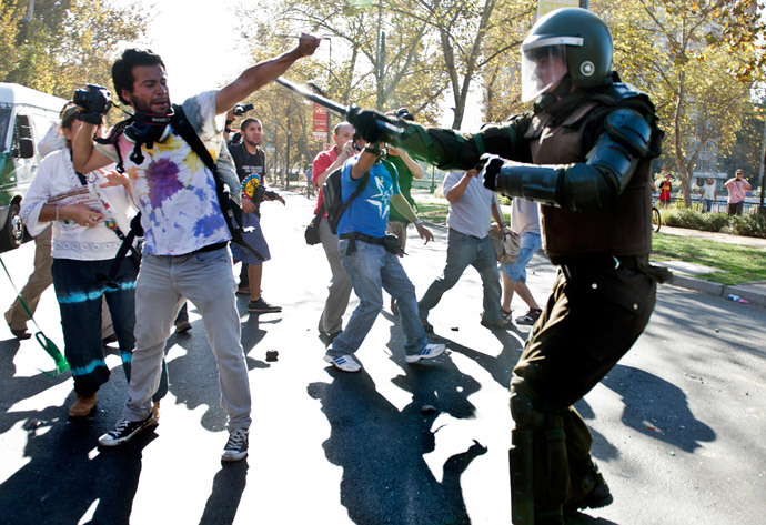 A demonstrator confronts a riot policeman during a protest to demand free and good quality education and a call for a Constituent Assembly, in Santiago, on March 22, 2014. (AFP Photo / Martin Bernetti)