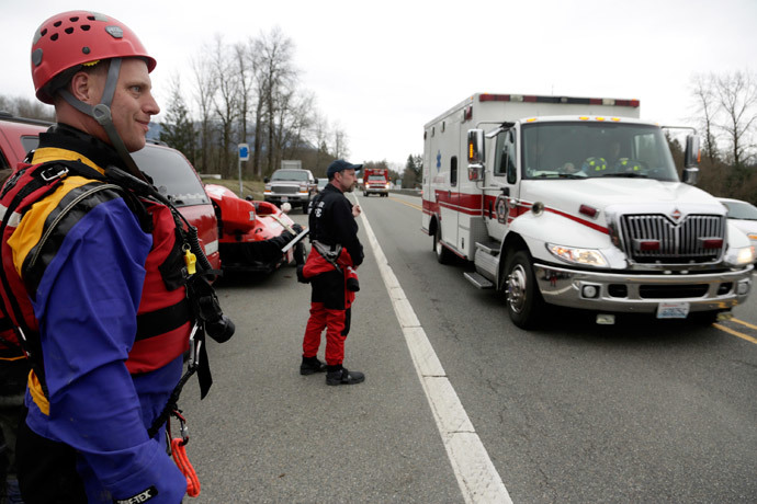 Members of a swift water rescue team look on as an ambulance drives past after a large mudslide blocked Highway 530 near Oso, Washington March 22, 2014. (Reuters / Jason Redmond)