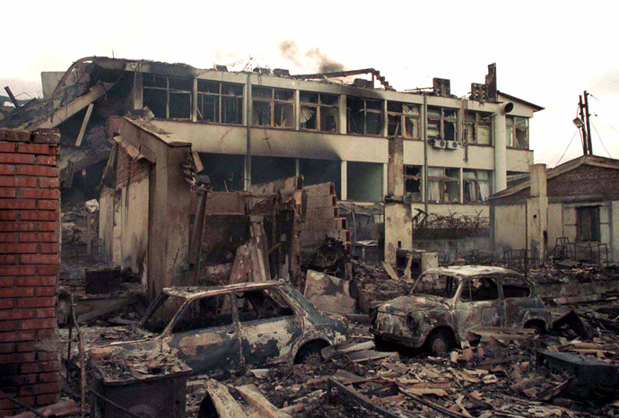 Smoke rises over the local red cross office destroyed in last night's NATO air strike on centre of Kosovo's capital Pristina March 29, 1999 (Reuters)