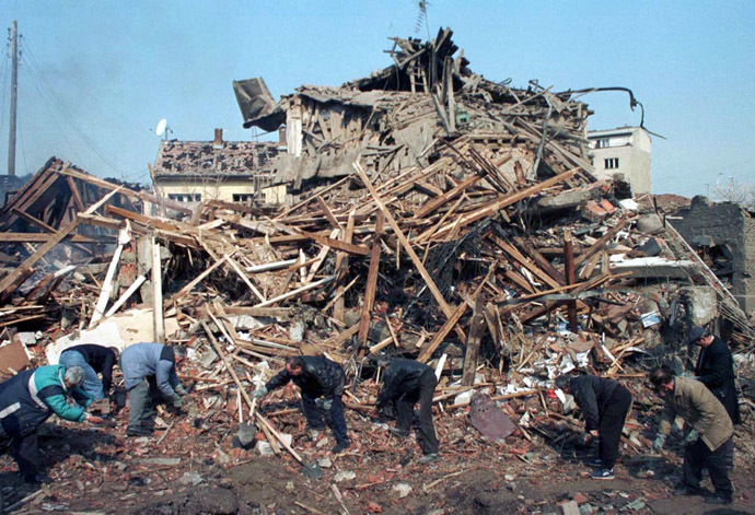 Pristina residents search through the rubble after a NATO missile hits the centre of Kosovo's capital early April 7. (Reuters)
