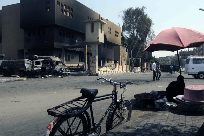 An Egyptian street vendor sits opposite a torched and vandalized police station on August 24, 2013 in the Kirdasah neighbourhood of Giza, on the outskirts of Cairo, that was attacked on August 14, resulting in the death of at least seven policemen following a crackdown by Egyptian security forces on protest camps and sit-ins held by supporters of the Muslim Brotherhood and ousted president Mohamed Morsi.(AFP Photo)