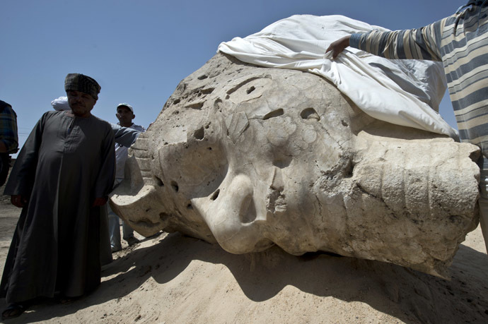 Egyptian archaeological workers stand next to a newly displayed alabaster head from an Amenhotep III statue in Egypt's temple city of Luxor on March 23, 2014. (AFP Photo)