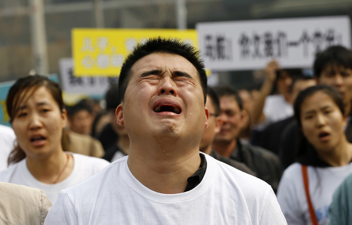 A family member of a passenger on board Malaysia Airlines MH370 cries as he shouts slogans during a protest in front of the Malaysian embassy in Beijing, March 25, 2014. (Reuters/Kim Kyung-Hoon)