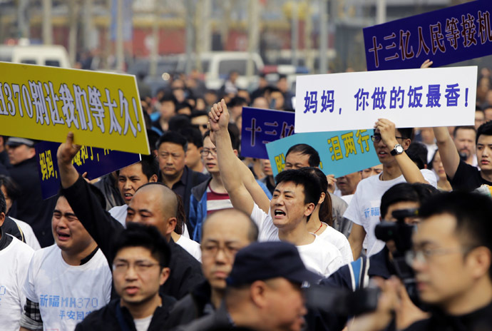 Family members of passengers aboard Malaysia Airlines MH370 shout slogans during a protest near the Malaysian embassy in Beijing, March 25, 2014. (Reuters/Jason Lee)