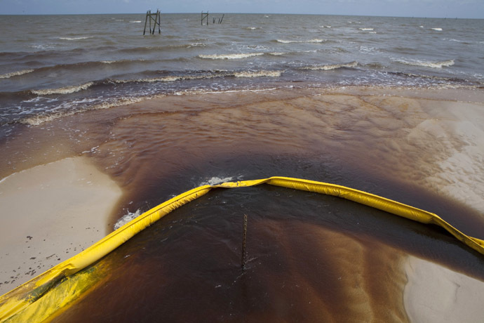 A protective boom is seen as oil from the Deepwater Horizon spill recedes back into the Gulf of Mexico after washing into a drainage canal in Waveland, Mississippi July 7, 2010. (Reuters/Lee Celano)