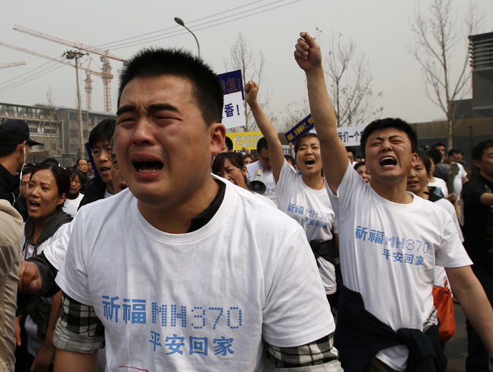 Family members of passengers onboard Malaysia Airlines MH370 cry as they shout slogans during a protest in front of the Malaysian embassy in Beijing March 25, 2014. (Reuters/Kim Kyung-Hoon)