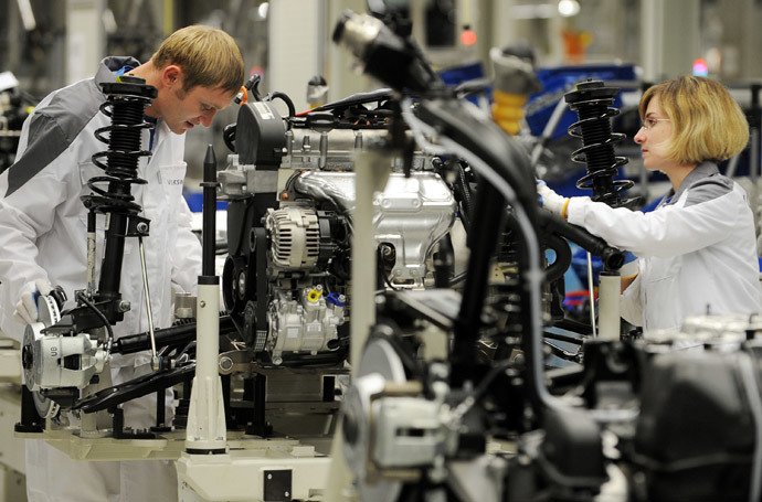 A Russian man and woman work on the assembly line of a Volkswagen plant in Kaluga (AFP Photo / Natalia Kolesnikova)