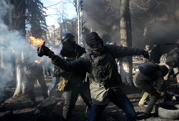 An anti-government protester throws a Molotov cocktail towards Interior Ministry members during clashes in Kiev, February 18, 2014 (Reuters / Maks Levin)