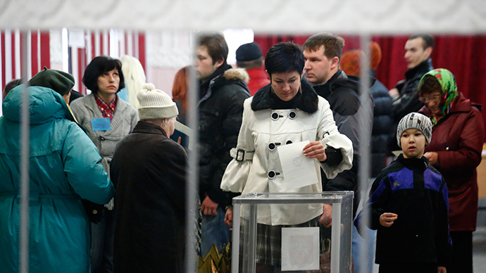 A woman is reflected in a mirror as she casts her ballot during voting in a referendum at a polling station in Simferopol March 16, 2014 (Reuters)