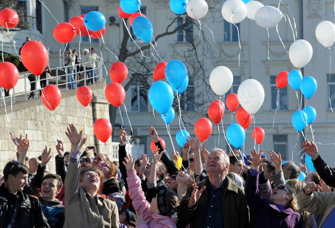 People launch balloons painted in the colors of the Russian flag during a flash mob in the Crimean city of Sevastopol on March 23, 2014. (AFP Photo / Viktor Drachev)