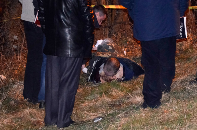 Police look at the body of Oleksander Muzychko, also known as Sashko Bily, lying on the ground near Rivne March 25, 2014. (Reuters / Olexandr Kursik)