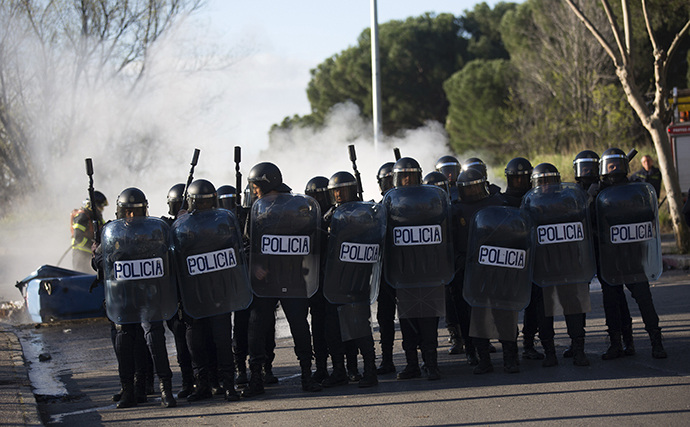Riot police officers stand beside a barricade with their shields at Complutense University on the second day of a 48-hour student strike to protest against rising fees and educational cuts in Madrid March 27, 2014. (Reuters / Andrea Comas)