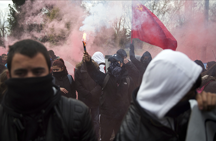 A student raises a flare during a protest at Complutense University on the second day of a 48-hour student strike to protest against rising fees and educational cuts in Madrid March 27, 2014. (Reuters / Andrea Comas)