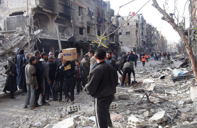 Residents of Syria's besieged Yarmuk Palestinian refugee camp, south of Damascus, stand amidst debris as they wait to receive food parcels on March 24, 2014. (AFP Photo / Rami Al-Sayed)