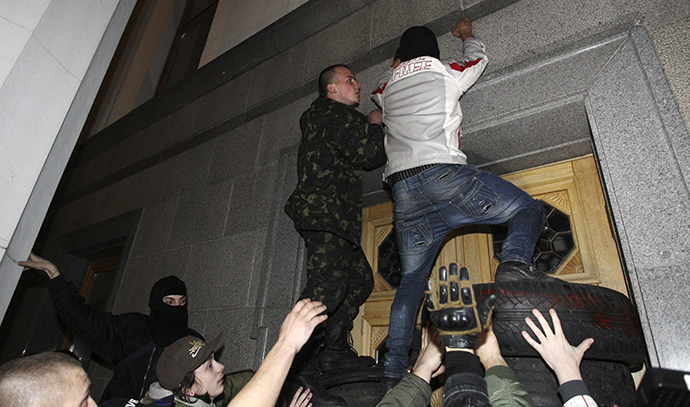 Men climb onto the parliament building as activists of the Right Sector movement and their supporters gather to demand the immediate resignation of Internal Affairs Minister Arsen Avakov, in Kiev March 27, 2014. (Reuters / Valentyn Ogirenko)