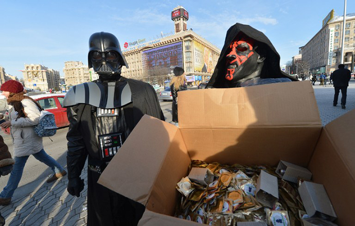 A leader of the Ukrainian Internet Party, wearing a Darth Vader outfit from the Star Wars saga, and an activist distribute goods on December 20, 2012 on Independence Square in Kiev. (AFP Photo / Sergey Supinsy)