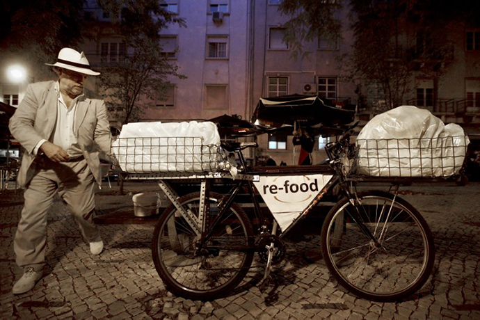 Hunter Halder walks toward his bicycle loaded with food that he collected in restaurants in Lisbon. (AFP Photo / Patricia De Melo Moreira)