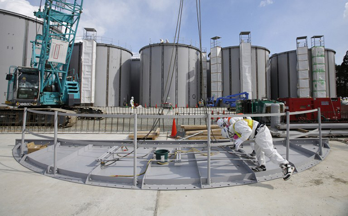 Men wearing protective suits and masks work in front of welding storage tanks for radioactive water, under construction in the J1 area at the Tokyo Electric Power Co's (TEPCO) tsunami-crippled Fukushima Daiichi nuclear power plant in Okuma in Fukushima prefecture (AFP Photo / Toru Hanai)