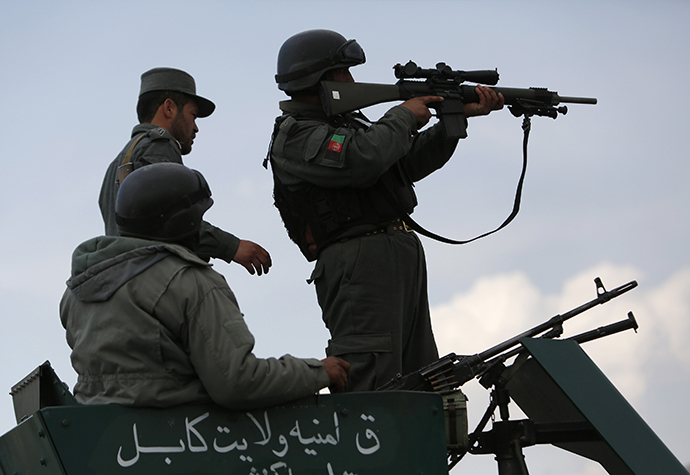 Afghan policemen take their positions atop a military vehicle near an election commission office during an attack by gunmen in Kabul March 29, 2014. (Reuters / Mohammad Ismail)