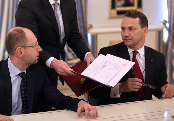 Poland's Foreign Minister Radoslaw Sikorski (R) and Ukraine's opposition leader Arseny Yatsenyuk (L) prepare to sign an EU-mediated peace deal with President Viktor Yanukovich, aiming to end a violent standoff that has left dozens dead and opening the way for a early presidential election this year, at the presidential headquarters in Kiev February 21, 2014. (Reuters / Konstantin Chernichkin)