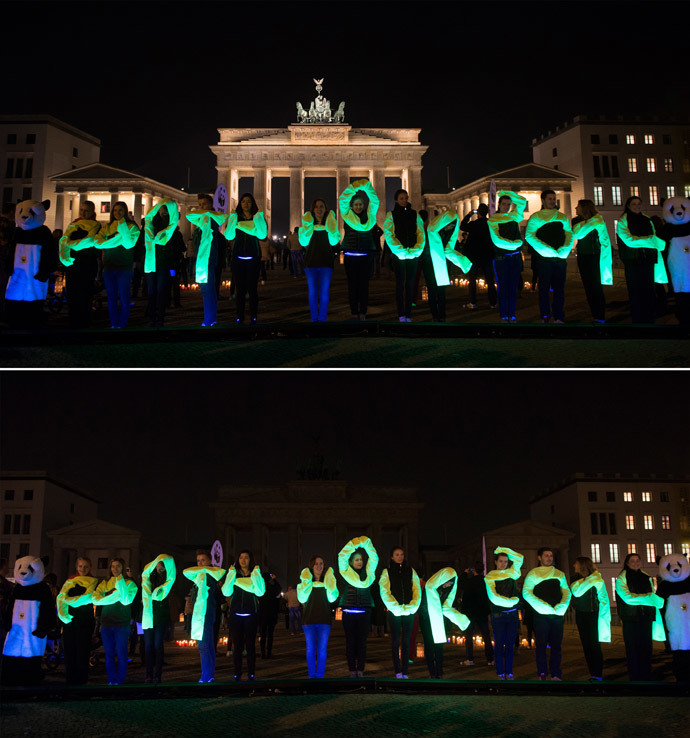 The combo picture shows activists of World Wide Fund (WWF) posing in front of the Brandenburg Gate during the Earth Hour environmental campaign in March 29, 2014 in Berlin. (AFP Photo / Johannes Eisele)