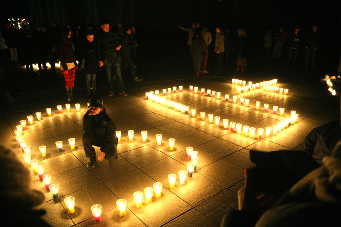 People attend a candle light vigil at Vilnius Cathedral as it stands unlit during Earth Hour in Vilnius on March 29, 2014.(AFP Photo / Petras Malukas)