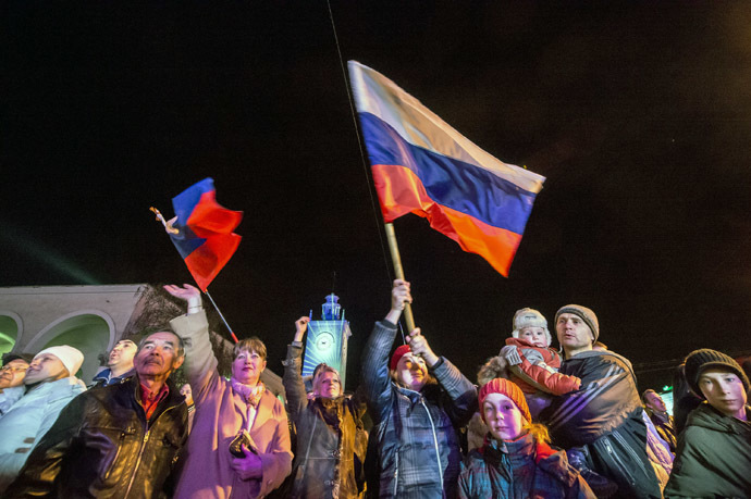 People celebrate the transition to Moscow time near a city clock tower at a railway station in Simferopol on March 30, 2014. (AFP Photo/Dmitry Serebryakov)