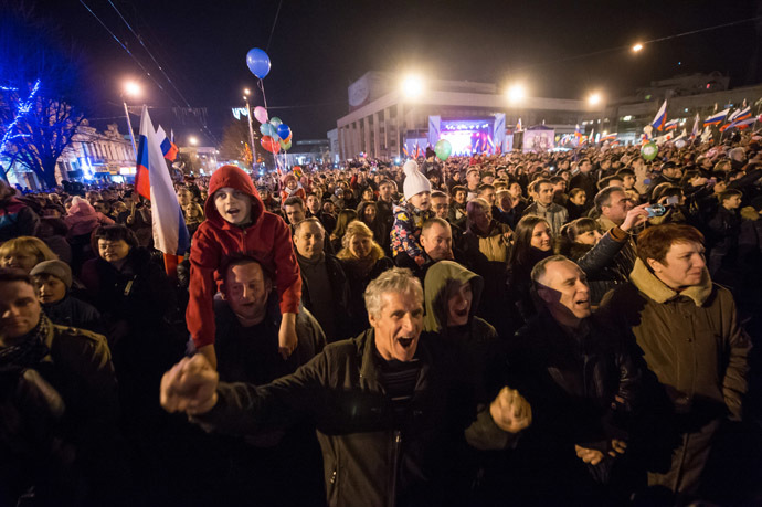 People wave Russian flags and cheer in the center of the Crimean city of Simferopol on March 21, 2014. (AFP Photo/Dmitry Serebryakov)